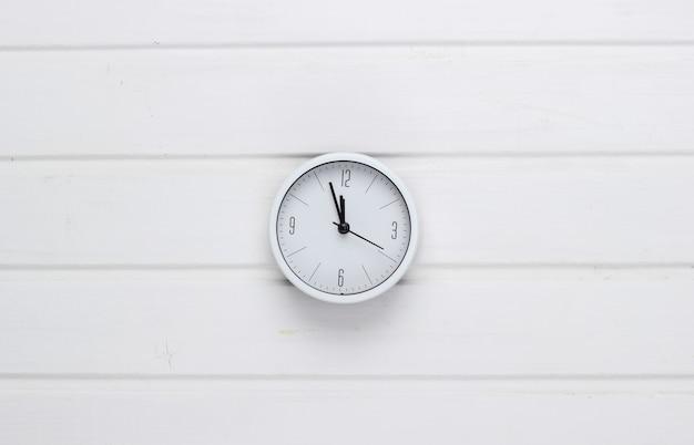 Relógio branco na superfície de madeira branca. o tempo está fugindo. vista do topo