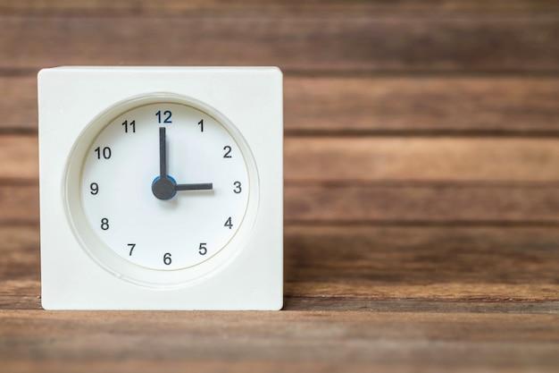 Relógio branco no fundo da placa de madeira marrom turva