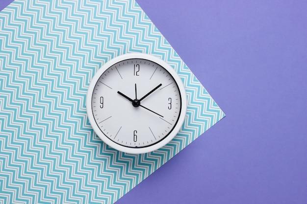 Relógio branco sobre fundo de papel. tiro de estúdio minimalista. vista do topo