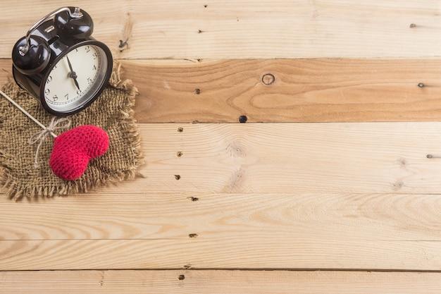 Relógio com coração de amor em fundo de madeira com copyspace