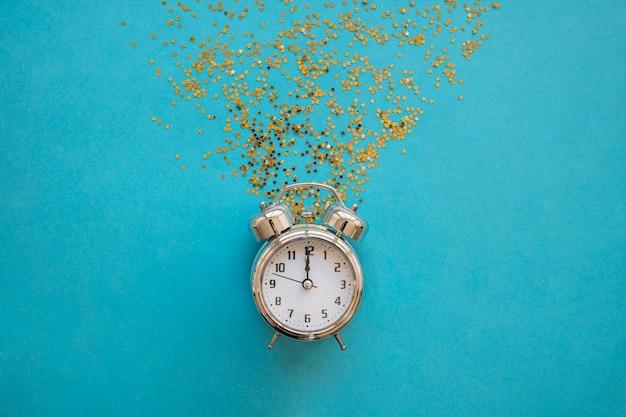 Relógio com lantejoulas brilhantes na mesa