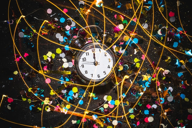 Relógio com lantejoulas na mesa preta