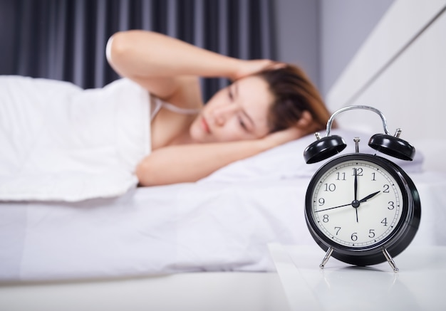 Relógio com mulher sem dormir na cama