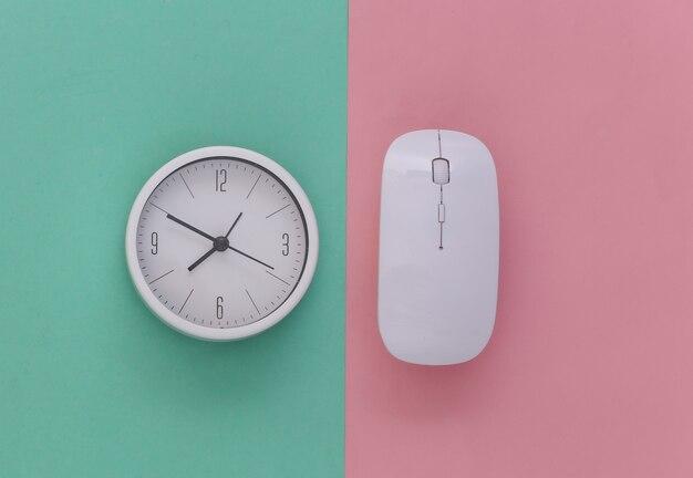 Relógio com o mouse do pc em fundo azul rosa. prazo de trabalho. vista do topo.