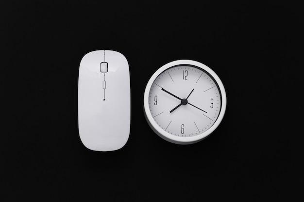 Relógio com o mouse do pc em um fundo preto. prazo de trabalho. vista do topo.