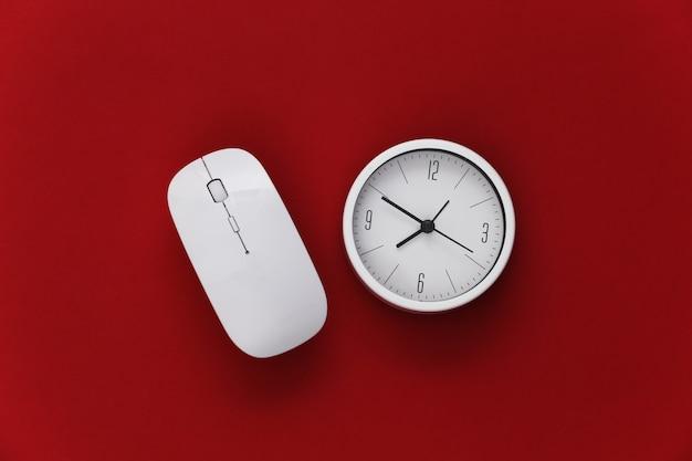 Relógio com o mouse do pc sobre fundo vermelho. prazo de trabalho. vista do topo.
