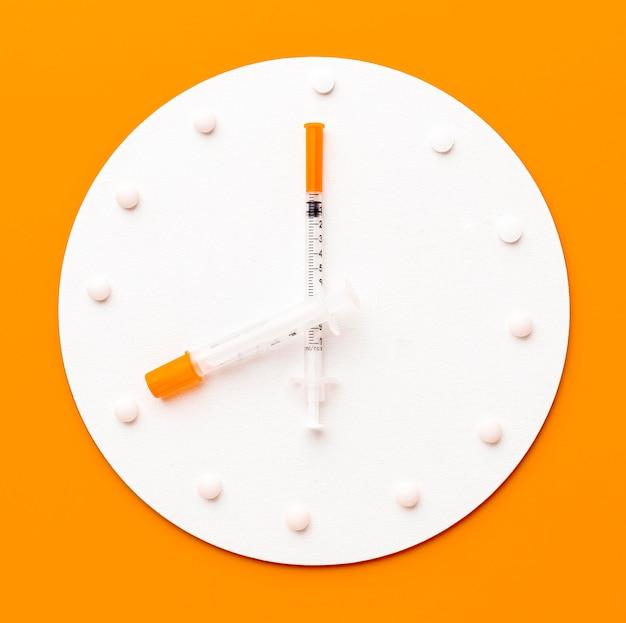 Relógio com pílulas e seringa
