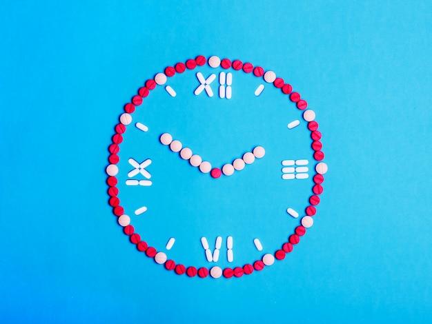 Relógio com setas de comprimidos médicos e comprimidos. conceito de saúde