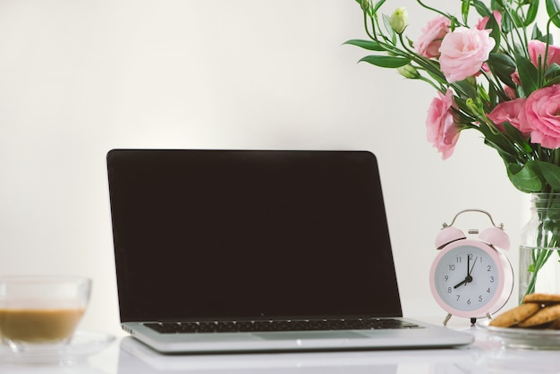 Relógio das 8h. cookies e flores na mesa do escritório com tela de apresentação do laptop.