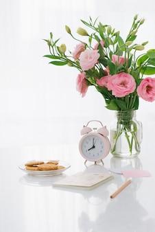 Relógio das 8h. cookies e flores na mesa.