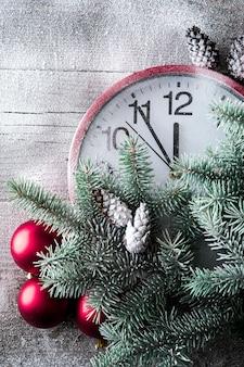 Relógio de ano novo em uma parede de madeira com uma árvore de natal e brinquedos