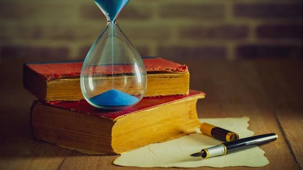 Relógio de areia com livros antigos e caneta com mapa de papel em cima da mesa de madeira.