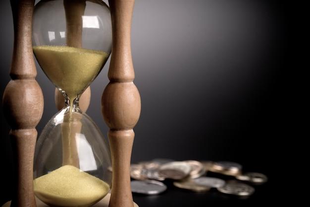 Relógio de areia e moedas em fundo preto