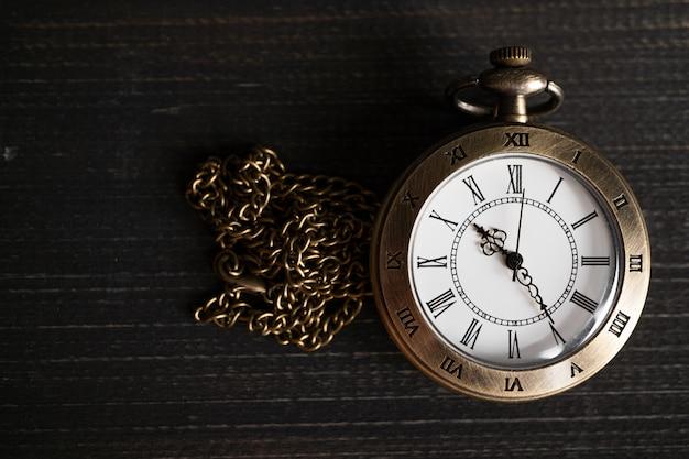 Relógio de bolso antigo colocado em uma madeira preta
