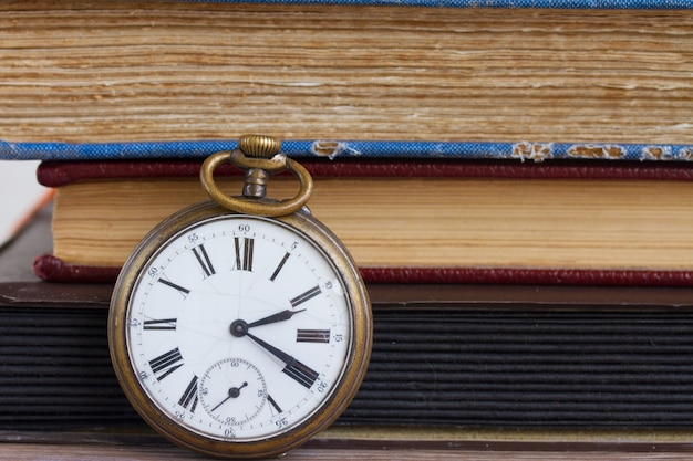 Relógio de bolso antigo com fundo de livros antigos