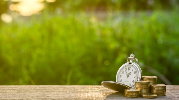 Relógio de bolso antigo e uma pilha de moedas de ouro