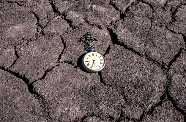 Relógio de bolso antigo em solo seco