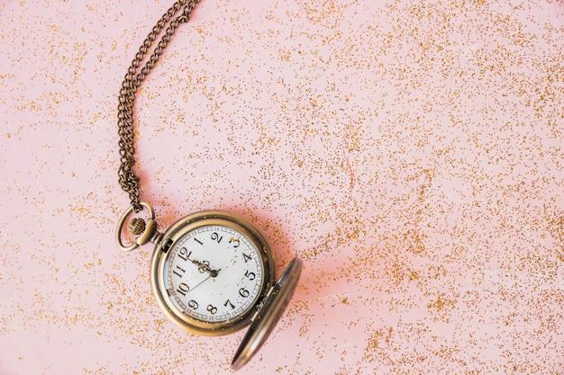 Relógio de bolso com lantejoulas na mesa