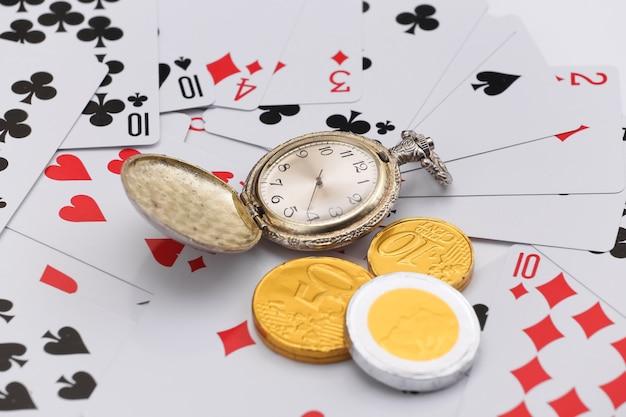 Relógio de bolso de ouro e moedas em cartas de jogar. tudo está em jogo