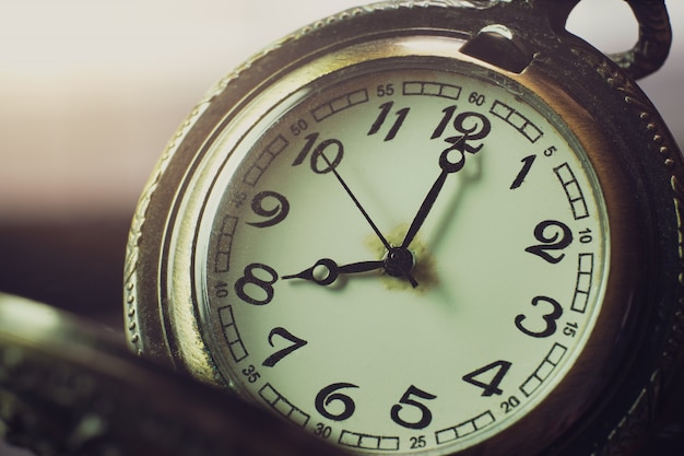 Relógio de bolso do close up na tabela e na luz solar. às 8 da manhã. horas da manhã. conceito de começar o trabalho hoje.