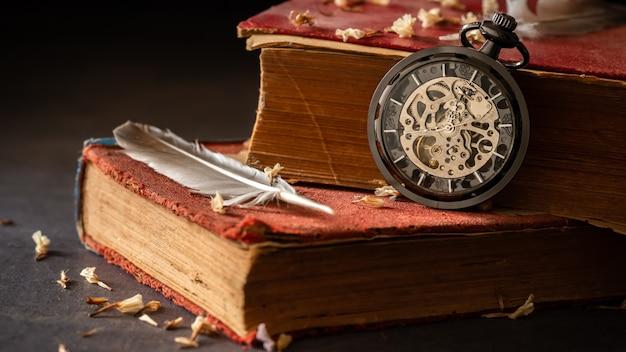Relógio de bolso do enrolamento em livros velhos com penas e pétalas secadas da flor na tabela de mármore na escuridão e na luz da manhã.