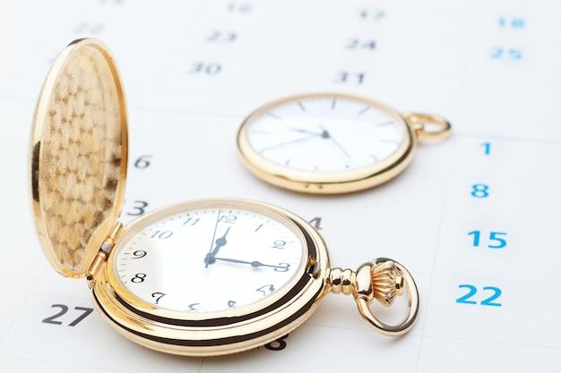 Relógio de bolso dois contra a parede do calendário. fechar-se.