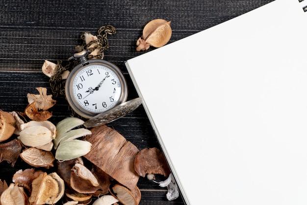 Relógio de bolso dourado colocado em folhas secas e caderno em branco na mesa preta retrô de madeira.