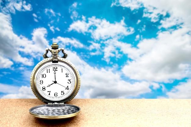 Relógio de bolso dourado do vintage luxuoso em de madeira sobre o céu azul, sumário para o conceito do tempo com espaço da cópia