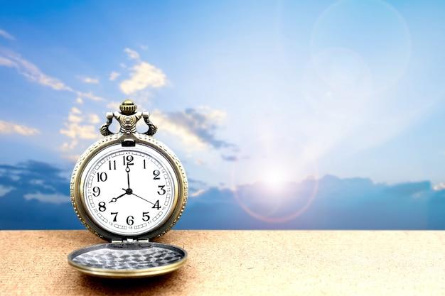 Relógio de bolso dourado vintage de luxo em madeira sobre o céu azul