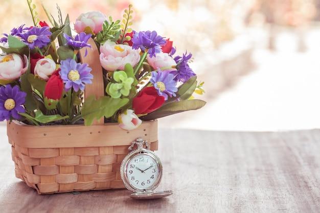 Relógio de bolso e planta de flores na cesta