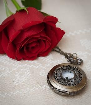 Relógio de bolso e rosa vermelha em um tecido