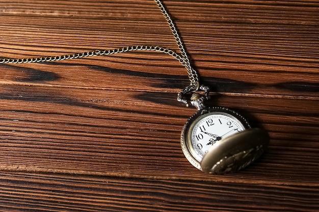 Relógio de bolso em superfície de madeira