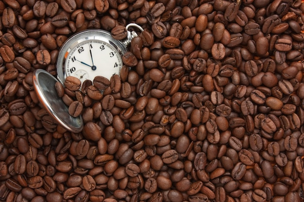 Relógio de bolso em uma pilha de grãos de café
