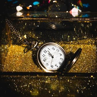 Relógio de bolso entre brilhos dourados
