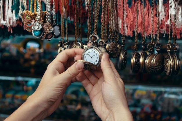 Relógio de bolso na mão de uma mulher.