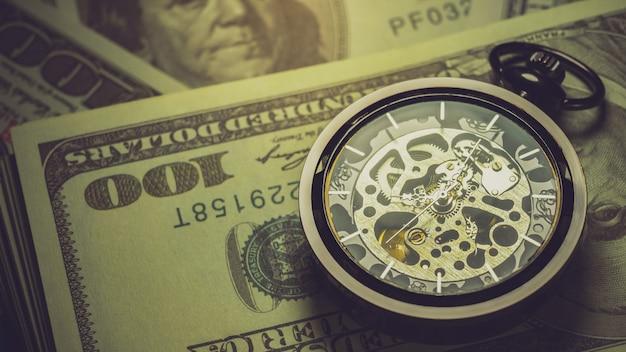 Relógio de bolso na nota de dólar.
