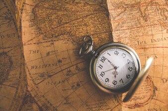 Relógio de bolso ou pingente de relógio no fundo do mapa vintage