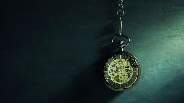Relógio de bolso que pendura no quadro preto e na luz solar na manhã. conceito de tempo e educação.