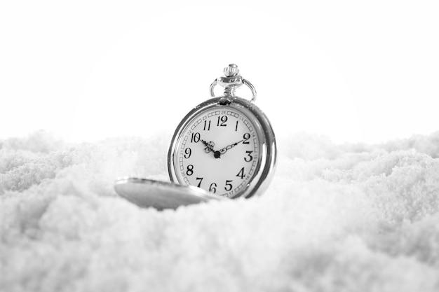 Relógio de bolso sobre fundo branco de neve