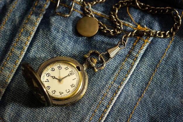 Relógio de bolso vintage é colocado sobre uma velha camisa jeans azul e o sol da manhã brilha no canto superior direito. o conceito de importância do tempo. close up e copie o espaço para texto ou seu artigo.