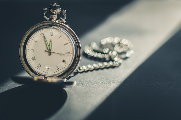 Relógio de bolso vintage na cadeia em um fundo escuro