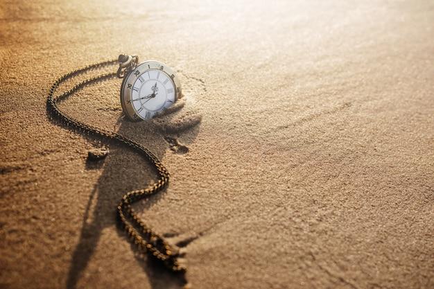 Relógio de bolso vintage na praia de areia dourada