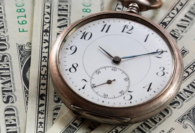 Relógio de bolso vintage nas notas de dólar