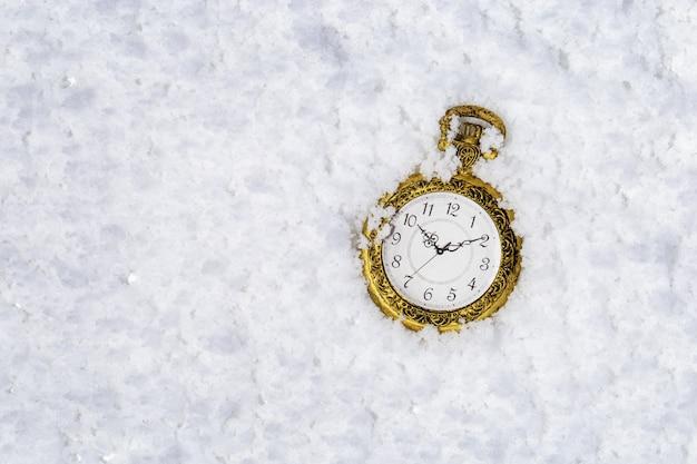 Relógio de bolso vintage ouro na neve