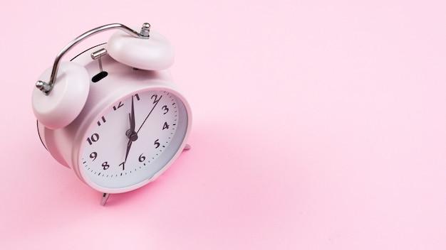 Relógio de close-up com fundo rosa