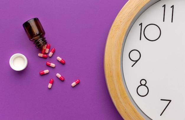 Relógio de close-up com pílulas na mesa