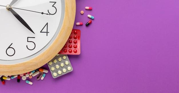 Relógio de cópia-espaço com comprimidos comprimidos