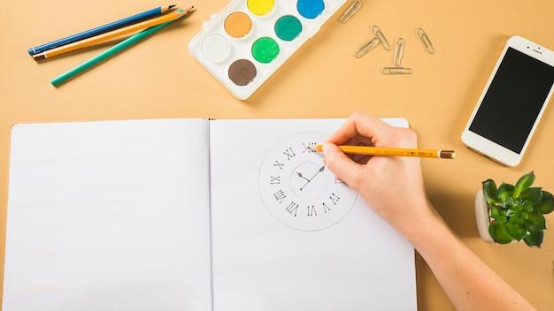 Relógio de desenho de mão de colheita no bloco de notas
