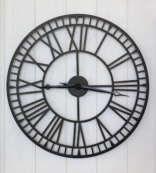 Relógio de estilo antigo no fundo da parede de prancha de madeira branca
