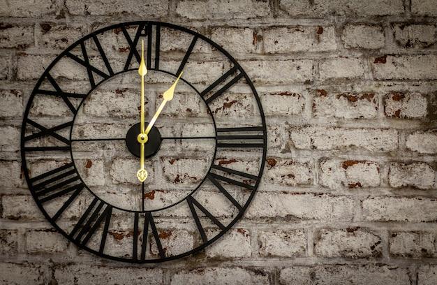 Relógio de ferro vintage na parede de tijolos com mãos de ouro